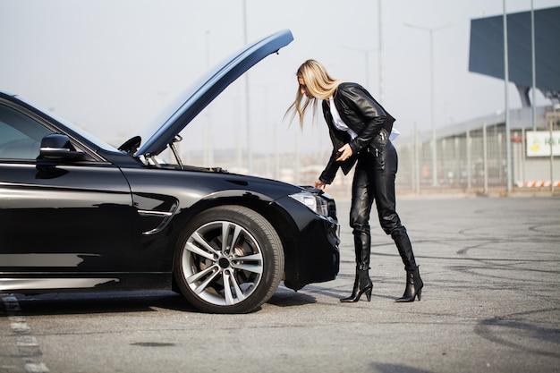 道路上の問題。スマートフォンで呼び出す壊れた車を持つ女性