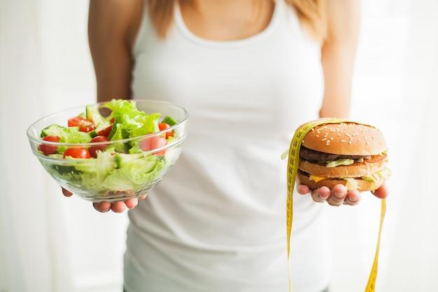 ダイエット。女性のハンバーガーとサラートを保持している体重計で体重を測定します。お菓子は不健康なジャンクフードです。ダイエット、健康的な食事、ライフスタイル。減量。肥満。