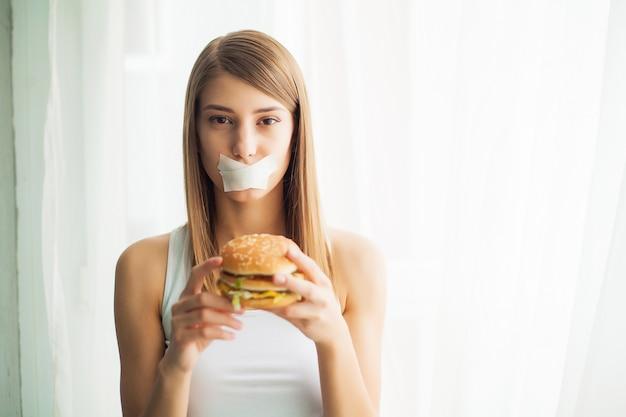 ジャンクフードを食べる彼女を防ぐ若い女性。健康的な食事のコンセプト
