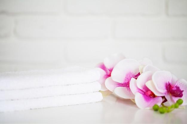 バスルームにコピースペースを持つ白いテーブルに白いタオル