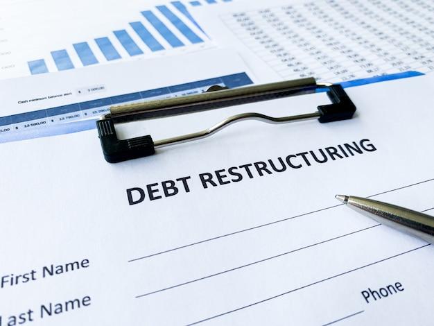 テーブル上のグラフと債務再編文書。