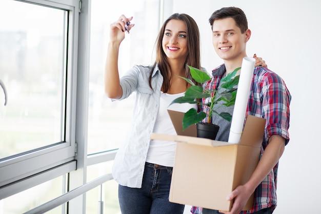 アパートを知らなかった。彼らの新しい家で幸せなカップル。屋内で抱き締める若いカップル