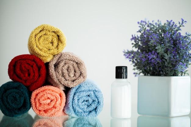 Цветные полотенца на белом столе на ванной