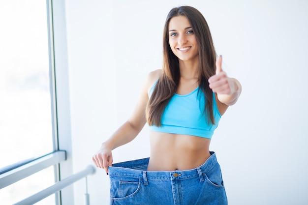ダイエットのコンセプト。彼女のウエストを測定するスポーツウェアの女性