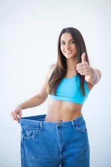 女性は彼女の減量を示し、彼女の古いジーンズを着ています