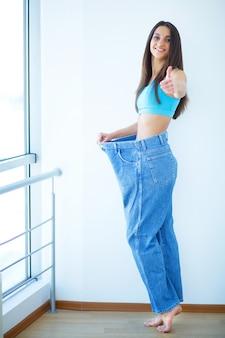 大きなジーンズと美しい若い女性