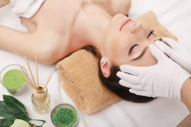 Молодая милая женщина наслаждаясь процедурой массажа лица