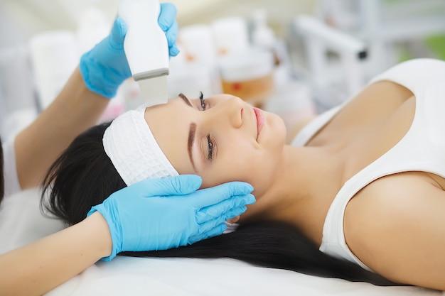 ボディケア。女性の顔の皮膚分析を受信します。美容
