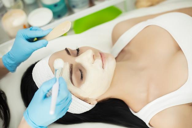 顔のマスクが彼女の顔に適用されている間ヘルススパでマッサージテーブルに横たわる女