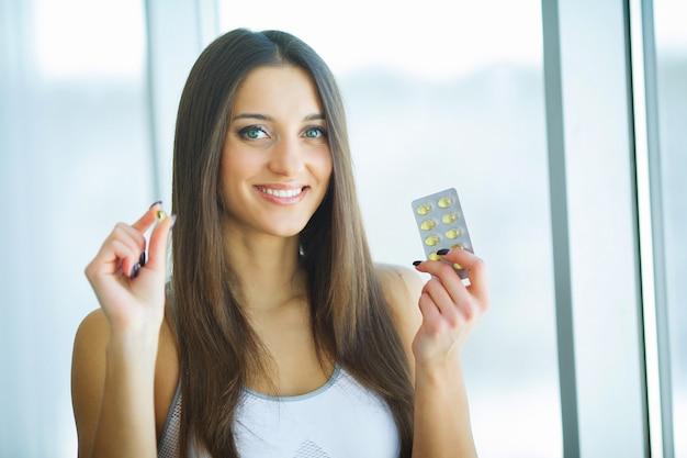 Красивая женщина улыбается, принимая таблетки витамина. пищевая добавка