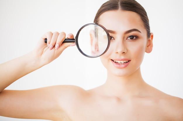 拡大鏡を通して見ると笑顔をクローズアップの女性