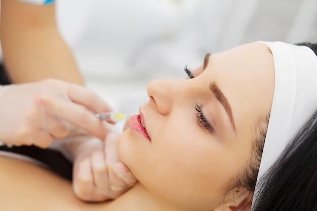 女性の唇に美容注射を行う美容師