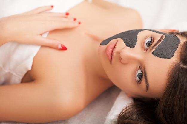 ビューティーサロンで顔の治療を得る美しい若い女性。