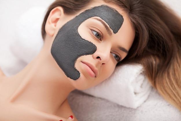 美容スパで自然な顔のマスクを持つ若い女性