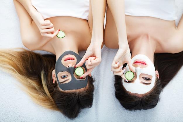 Портрет двух красивых девушек с кремом для лица на лицах и улыбкой