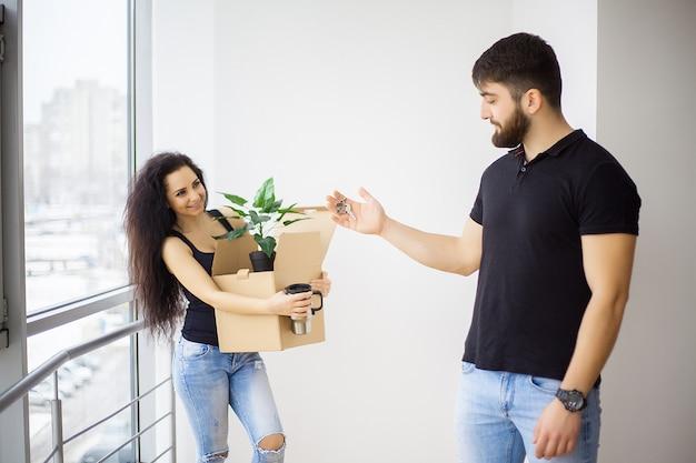 笑顔のカップルが新しい家で箱を開梱します。