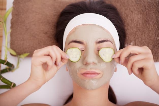 スライスキュウリと目を覆っている顔に粘土泥マスクの美しい若い女性。