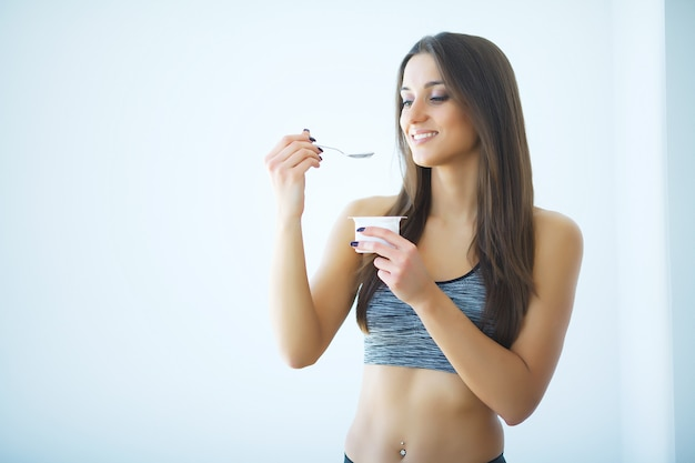 ダイエット。キッチンでヨーグルトを食べて幸せな若い女