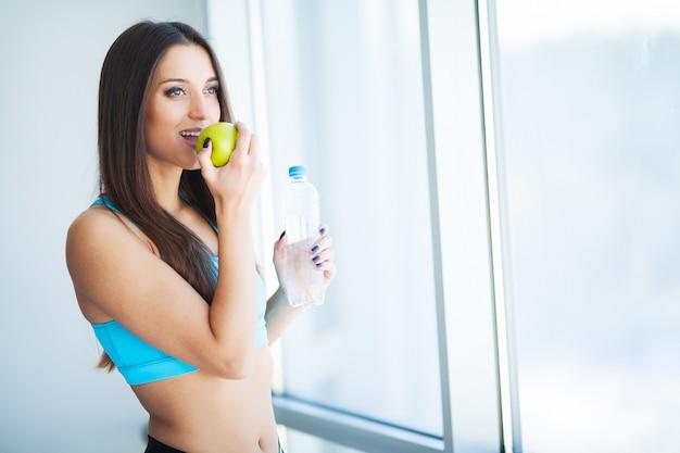ダイエットと飲料水。水のボトルを持つ女性