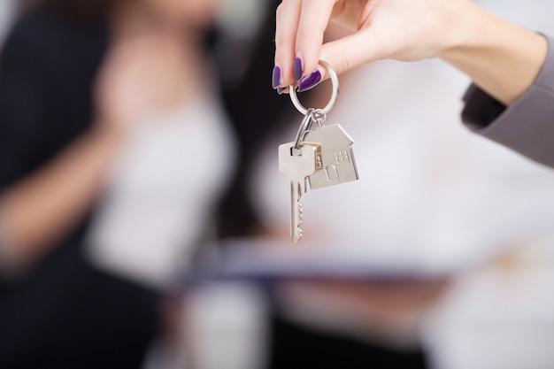 顧客に家の鍵を渡す不動産業者