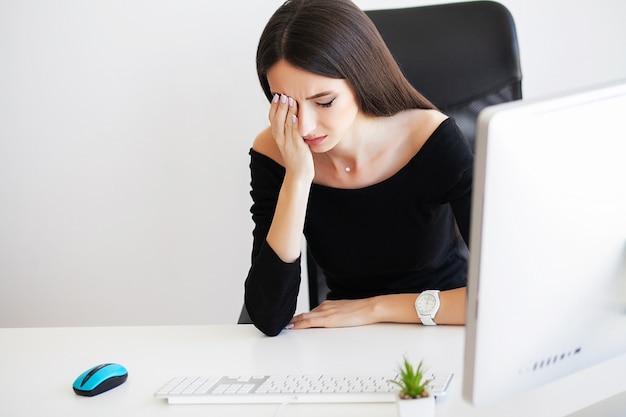 彼女のオフィスの痛みに苦しんでいる美しい女性実業家