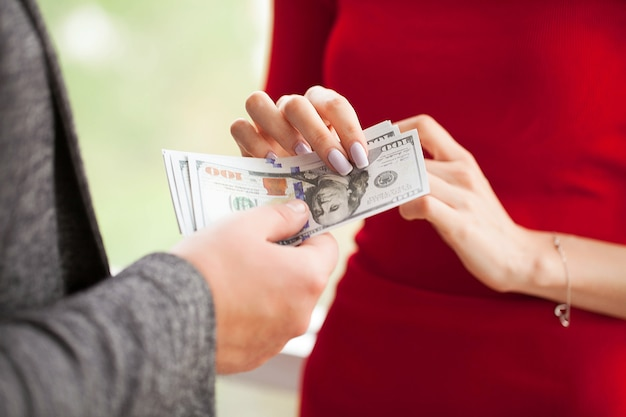 ビジネスの女性は男性にお金を与えます。赤い服を着た女性