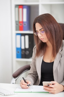 いくつかのドキュメントを通過する彼女の仕事の机に座って美しい若い女性のショット