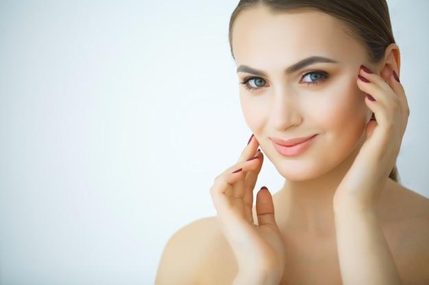 美容スキンケア。化粧品のフェイスクリームを適用する美しい女性