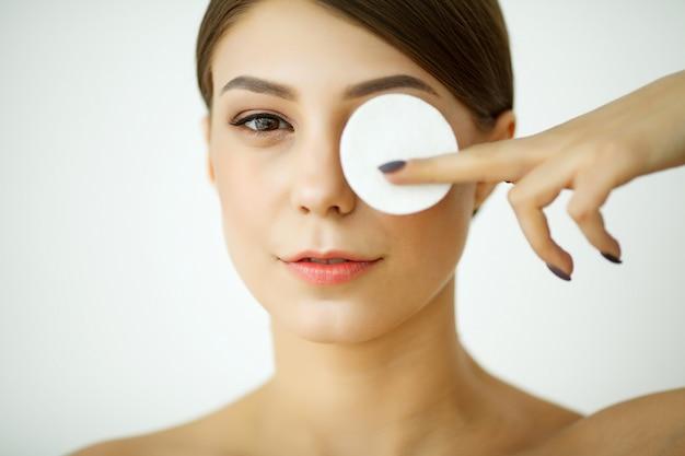 スキンケア。バスルームで顔を洗うローションを持つ若い女性