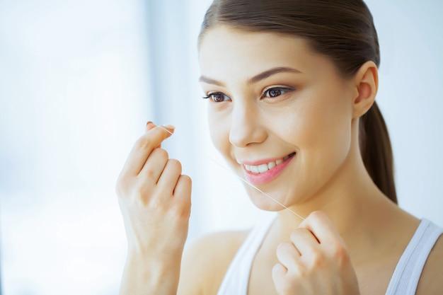 美容と健康。白い歯を持つ美しい少女は、デンタルフロスで歯をきれいにします。美しい笑顔を持つ女性。歯の健康