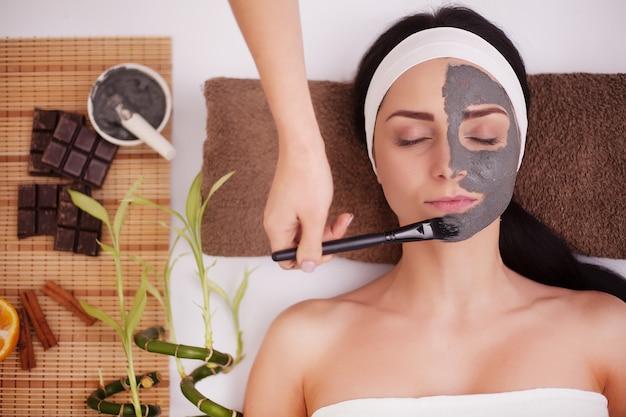 Нанесение маски на лицо женщины в салоне красоты