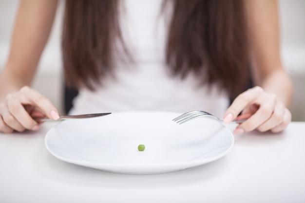 ダイエット。拒食症に苦しんでいます。エンドウ豆をフォークに乗せようとしている女の子の画像をトリミング