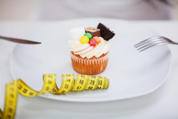 不幸で空腹の表現、スタジオで禁じられた食べ物を見て、おいしいクリームのタルトケーキとプレートの前に座っている若いダイエット女性