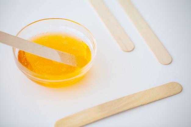 ワックス。ビューティーサロンで砂糖漬け用ペースト。ワックスとスティックのトップビューで概念脱毛。