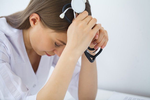 医師。病院のオフィスで悲しいまたは泣いている女性看護師