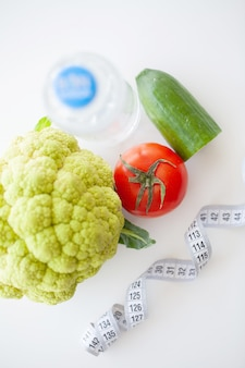 ダイエット。フィットネスと健康食品のダイエットコンセプト。野菜とバランスの取れた食事。新鮮な緑の野菜、測定テープ。閉じる