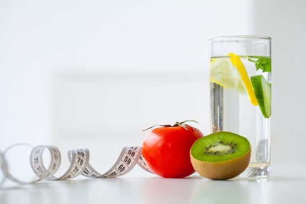 Рацион питания. фитнес и концепция здорового питания диета. сбалансированная диета с фруктами. свежие фрукты и стакан воды, измерительная лента. крупный план