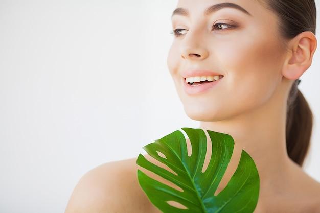 Спа уход. молодая красивая брюнетка с большими зелеными листьями