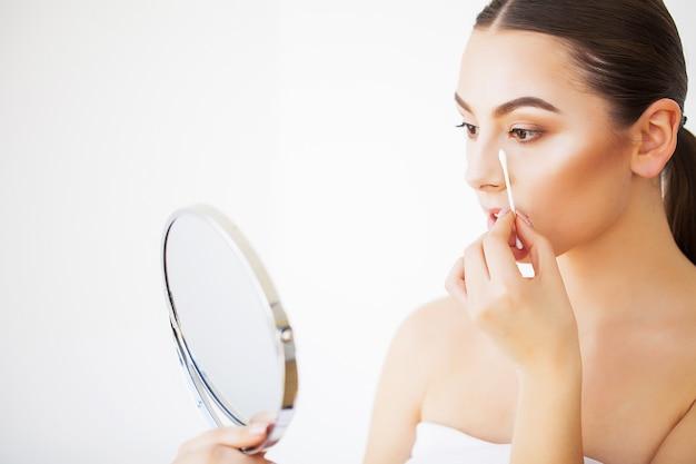 スキンケア。屋内で鏡で見ている新鮮な健康的な肌とセクシーな若い女性の肖像画