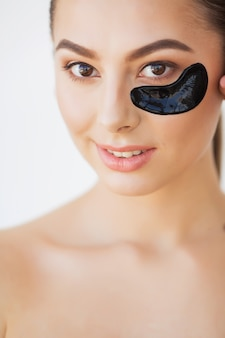 目の下のマスクを持つ女性美容顔。新鮮な顔の肌に自然なメイクと黒いコラーゲンパッチを持つ美しい女性