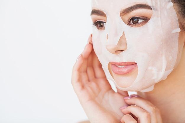 スキンケア。彼女の顔にシートマスクを持つ美しい少女