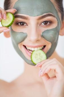 スキンケア。彼女の浴室でキュウリを保持している化粧品の粘土マスクを持つ若い女性