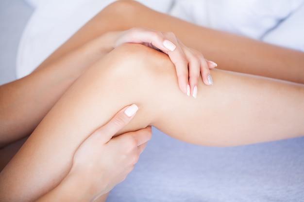 手の痛み。ストレスで。膝の痛みに苦しんでいる女性ランナーはベッドの上に座る