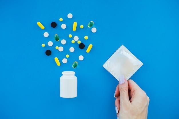経口避妊薬と包装されていないコンドーム。着色された丸薬とカプセル。薬局のテーマ、パッケージ内の抗生物質を含むカプセルの丸薬