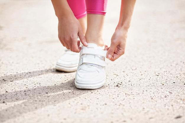 フィットネス。靴ひもを締める女性ランナー。靴の道路のクローズアップで実行されているランナーの女性の足