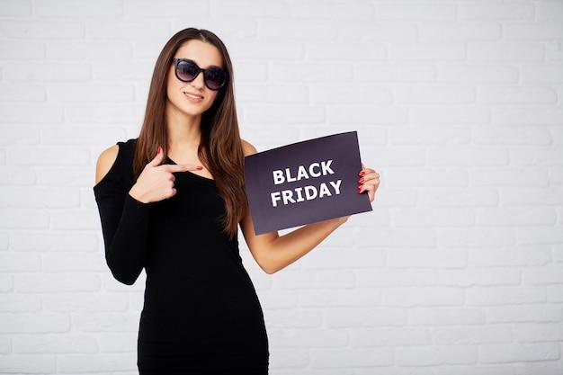 ショッピング。ブラックフライデーのセールで割引ブランクを保持している女性