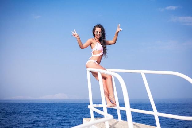 若い女性が船の甲板から海を賞賛します。海のクルーズ、旅行と休暇、世界一周旅行