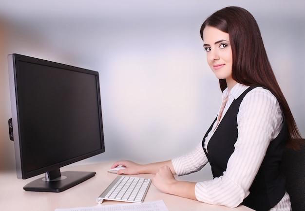 オフィスでコンピューターを使用して美しい成熟した女性実業家