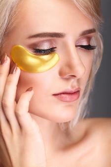 目の下のマスクを持つ女性美容顔。自然な化粧とゴールドコラーゲンパッチを持つ美しい女性。