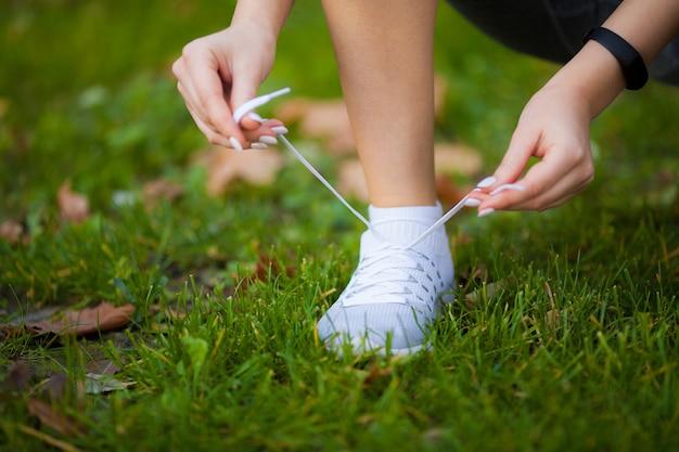 靴ひもを締める女性ランナー。靴の道路のクローズアップで実行されているランナーの女性の足